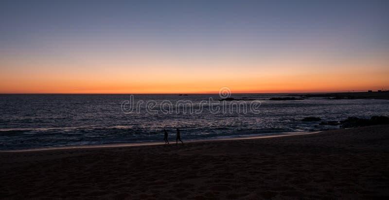 在海滩的美丽的梯度天空在日落在葡萄牙 跑步沿海岸线的现出轮廓的人民 免版税库存图片
