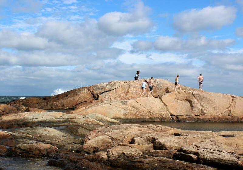 在海滩的美好的天与蓝天、云层和小组青年人上升在岩石的, Narragansett,罗德岛州 免版税库存图片