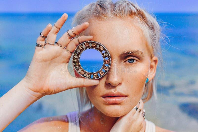 在海滩的美好的年轻时装模特儿 拿着小镜子的boho模型接近的画象在她的眼睛 库存照片