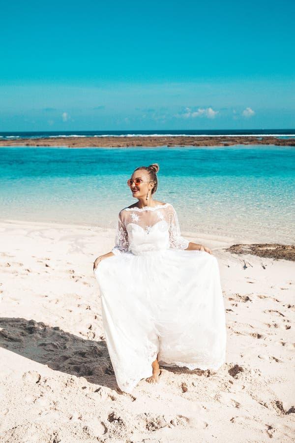 在海滩的美好的新娘跳舞在蓝天和海后 免版税库存图片