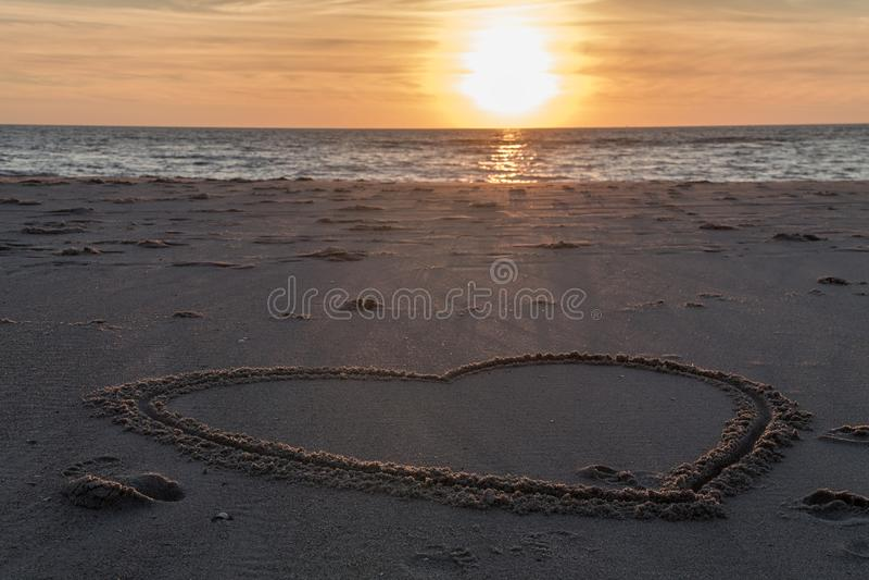 在海滩的美好的日落与木堆和心脏图画在沙子 库存照片
