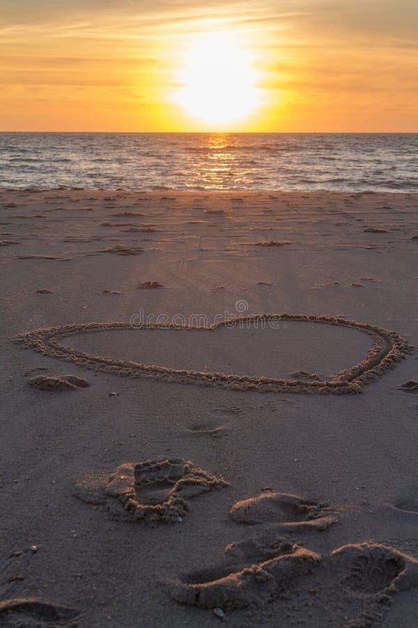 在海滩的美好的日落与木堆和心脏图画在沙子 库存图片