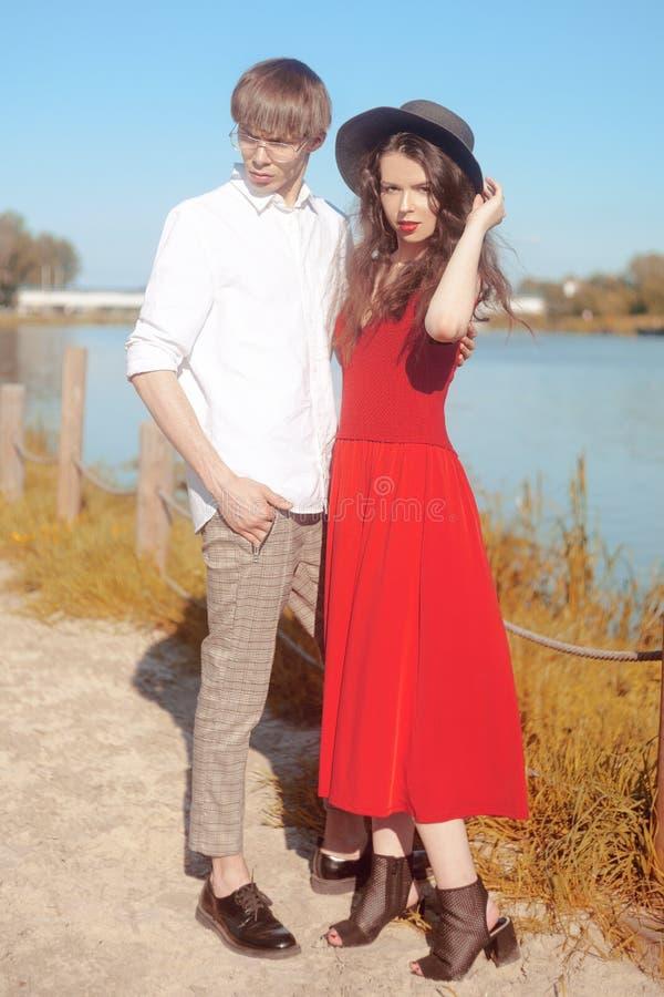 在海滩的美好的时兴的夫妇在河附近 时兴的行家 一个红色礼服和黑大帽子的女孩 免版税库存图片