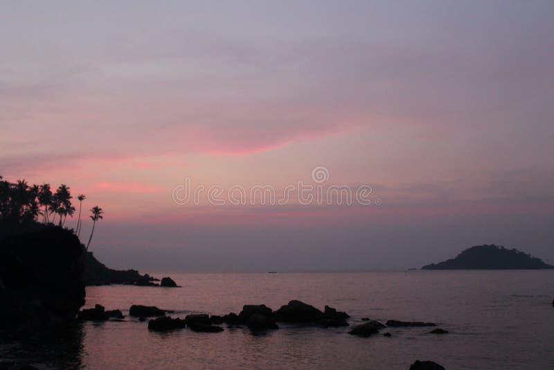 在海滩的美妙的日落与在晚上时间的壮观的天空 免版税库存图片