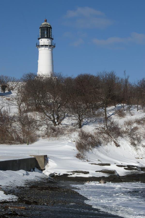 在海滩的老灯塔塔在斯诺伊冬天 免版税库存照片
