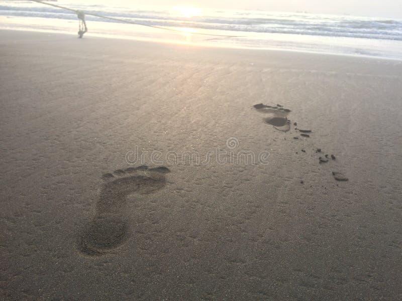在海滩的脚印,在海浪和绳索清扫的白色沙子 免版税库存照片