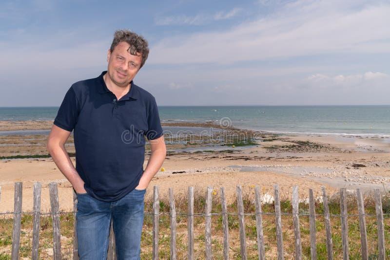 在海滩的英俊的愉快的人身分在Isle de Re法国 图库摄影
