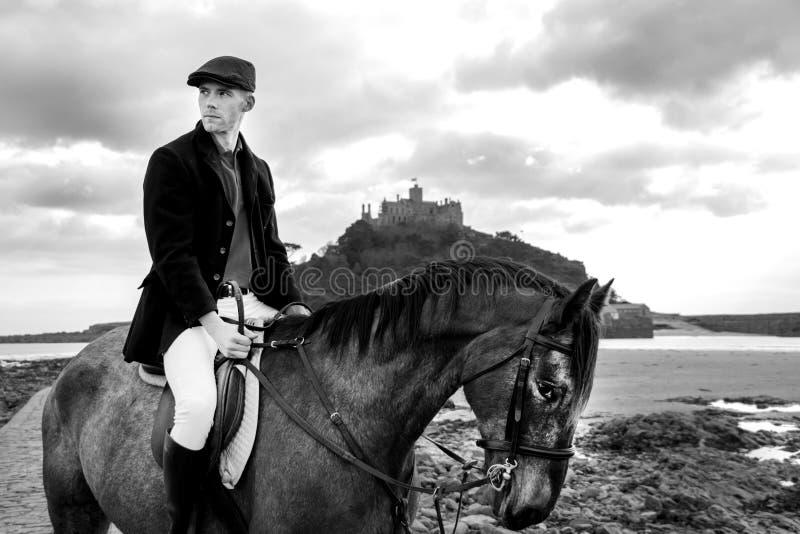在海滩的英俊的雄性马车手骑乘马以与圣迈克尔` s登上的传统时尚在背景中 库存图片