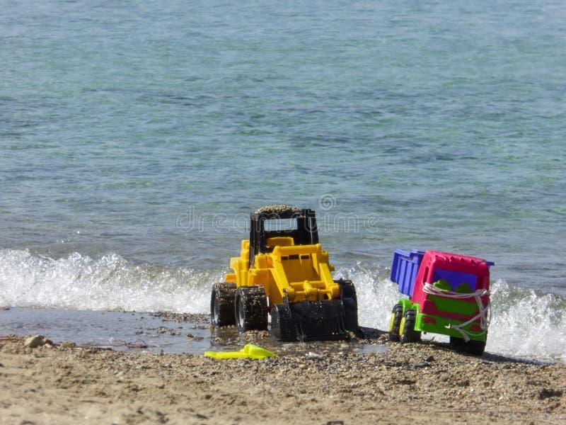 在海滩的被放弃的塑料玩具 库存照片