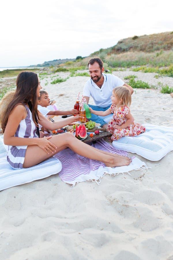 在海滩的野餐在样式boho、食物和饮料构想的日落 库存图片