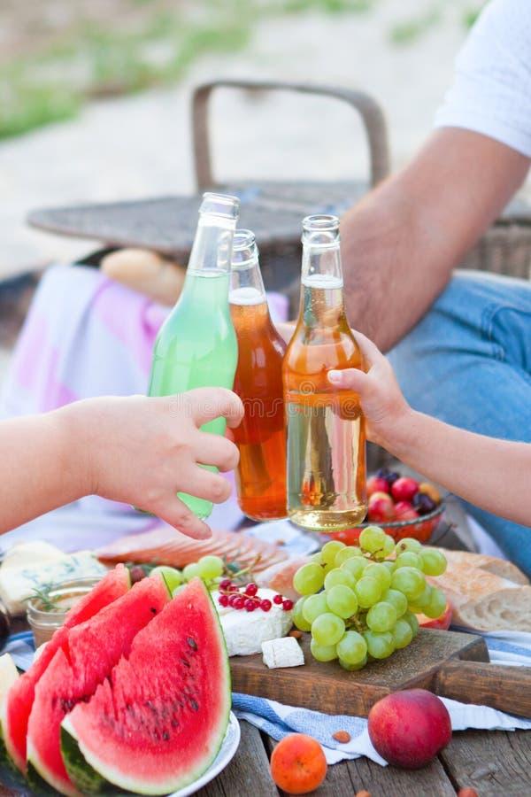 在海滩的野餐在样式boho、食物和饮料构想的日落 免版税库存照片