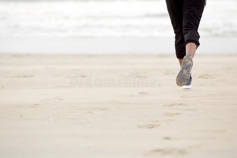 在海滩的非裔美国人的女性赛跑与体操鞋 库存照片