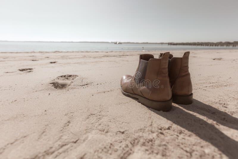 在海滩的鞋子身分 免版税库存照片