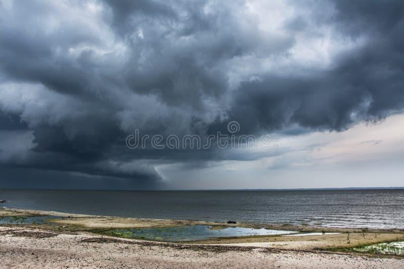 在海滩的风雨如磐的云彩,海 免版税库存照片