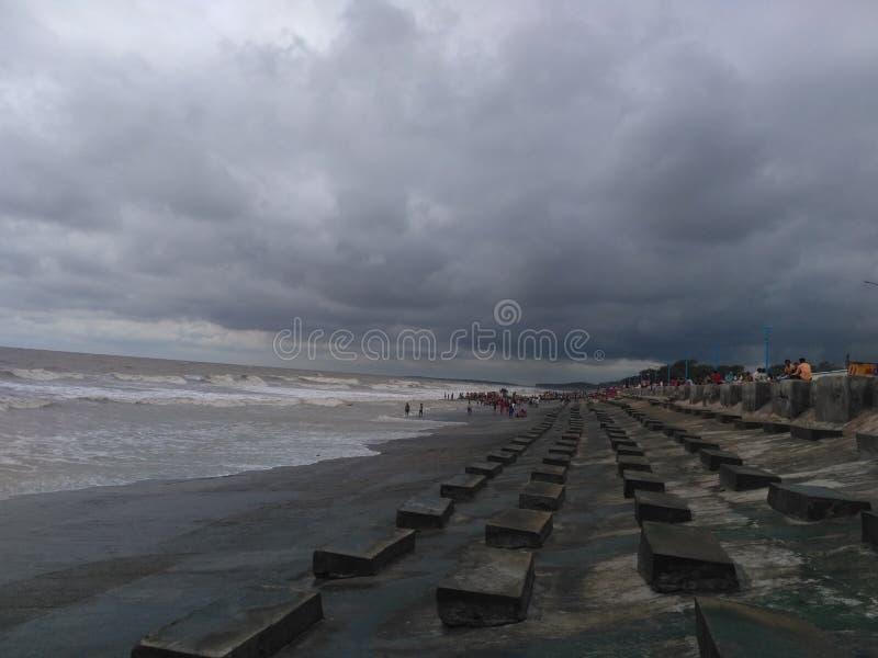 在海滩的黑暗的时间云彩 库存照片