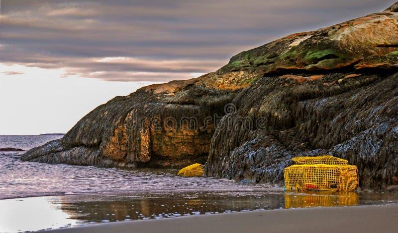 在海滩的龙虾陷井在有浪潮和岩石峭壁的缅因 库存照片