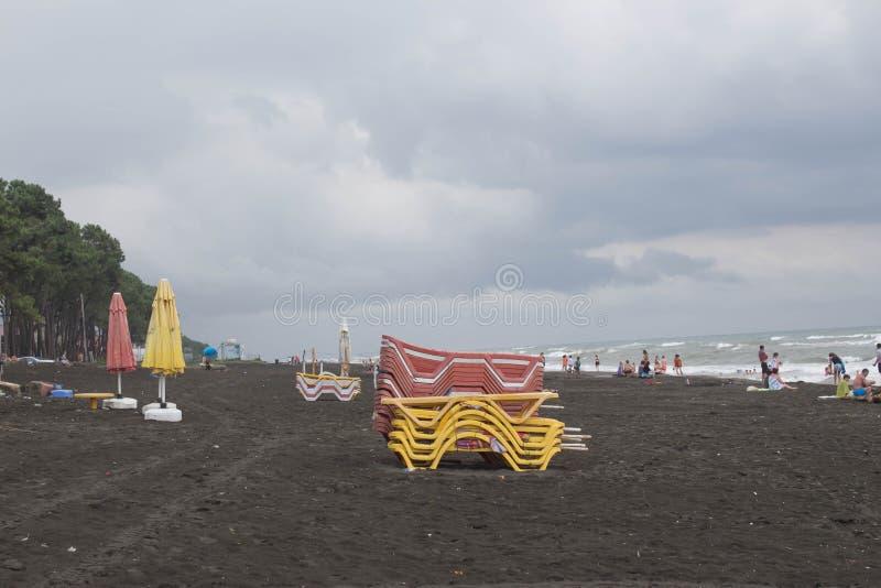 在海滩的Sunbeds 多云天气,海滩的阴暗未认出的人 库存图片
