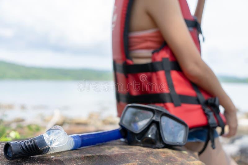 在海滩石头的潜水的面具和废气管齿轮与放松在度假夏天休假的妇女佩带的救生衣 海滩假期废气管 免版税库存图片