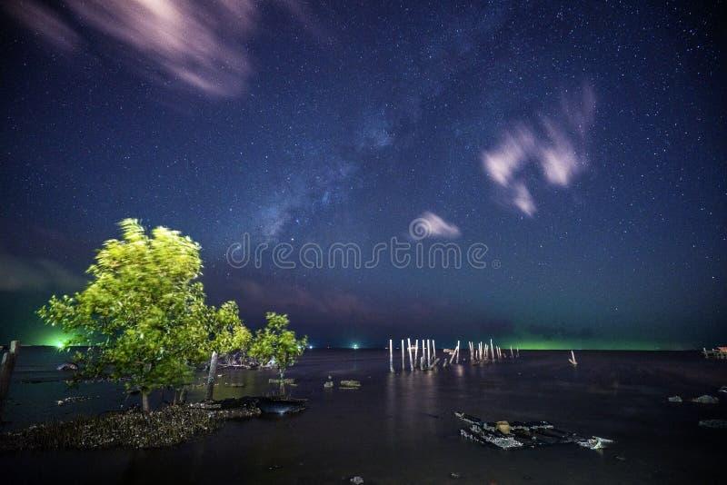 在海滩移动的云彩的银河在天空 免版税库存照片