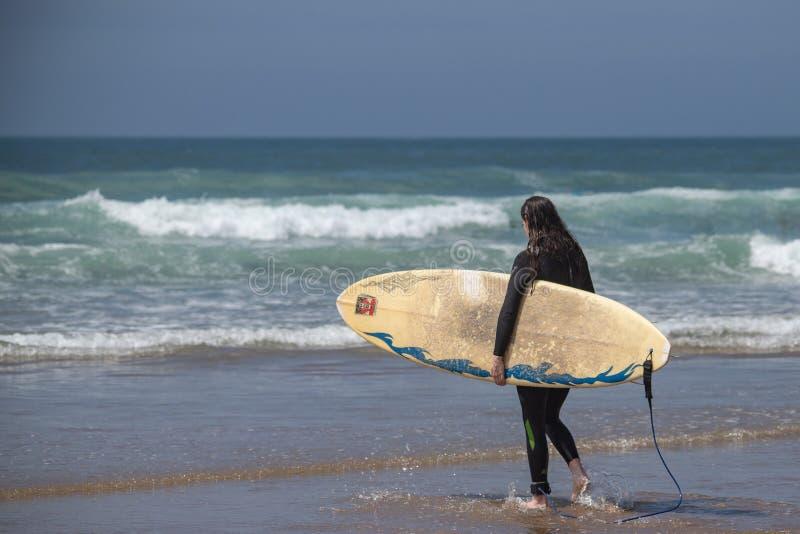 在海滩站立的女性冲浪者看对海 库存图片