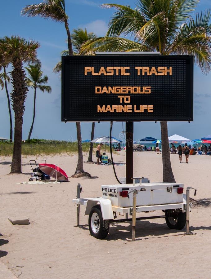 在海滩警告的流动标志塑料是危险的对海洋生物 库存图片