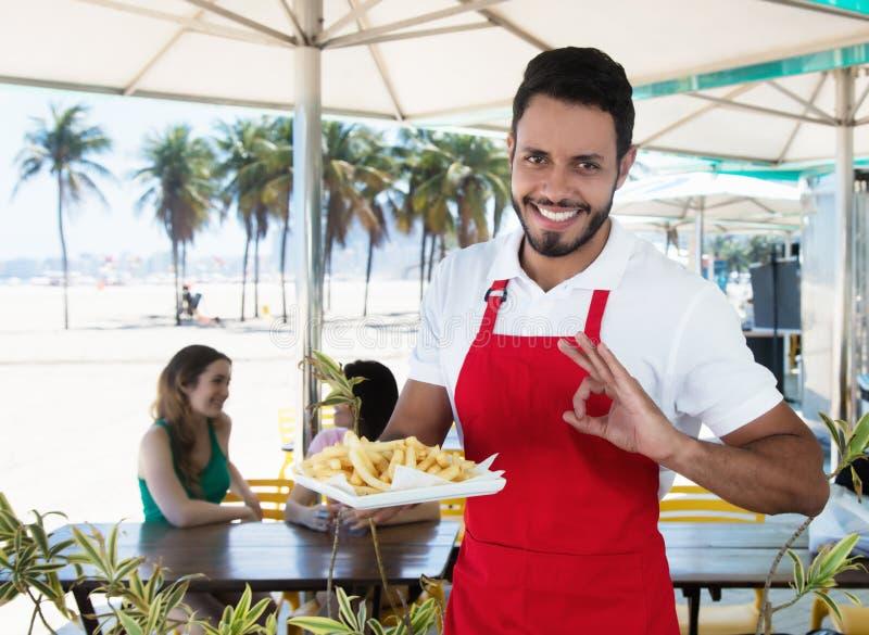 在海滩酒吧的愉快的侍者服务炸薯条 免版税库存照片