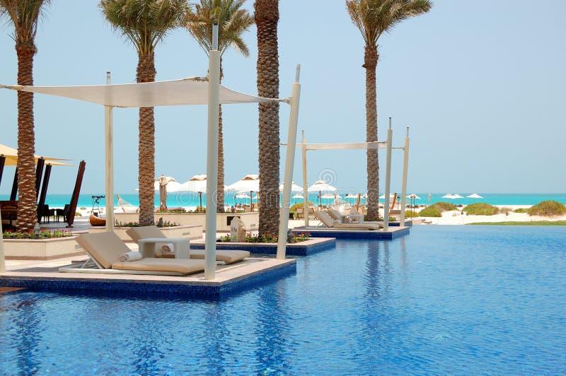 在海滩附近的游泳池在豪华旅馆 免版税库存照片
