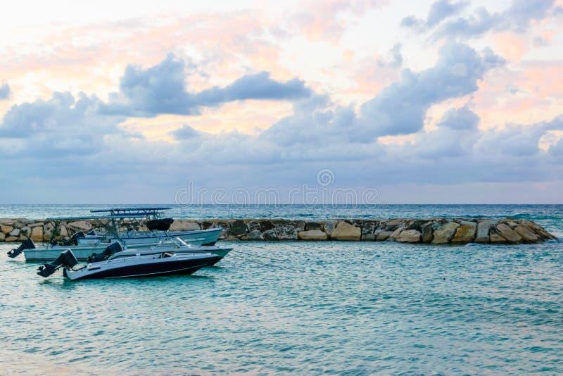在海滩靠码头的快艇汽艇在热带加勒比岛上的日落 假日豪华旅游胜地设置 免版税库存照片