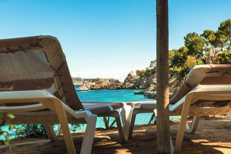 在海滩,太阳椅子的夏天休假有美好的海视图 免版税库存图片