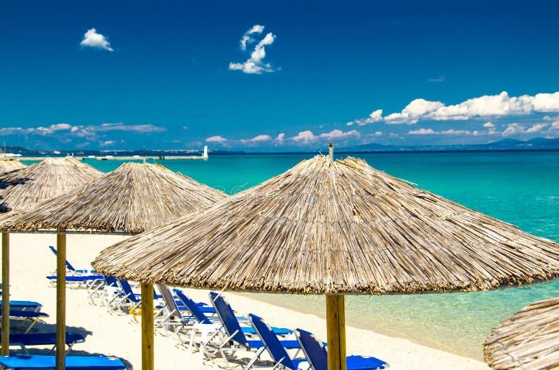 在海滩,蓝色天堂水,Halkidiki,Greec的黄色伞 库存图片