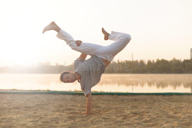 在海滩sunris的运动capoeira执行者锻炼训练 免版税库存照片