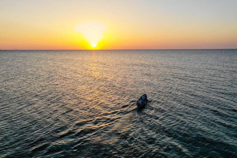 在海的一个小船航行,清早,作为背景的美好的日出 鸟瞰图海景 钓鱼在a的本地人 免版税图库摄影