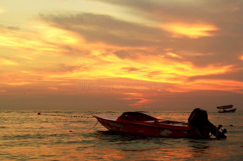 在海的一条小船在日落期间 库存图片