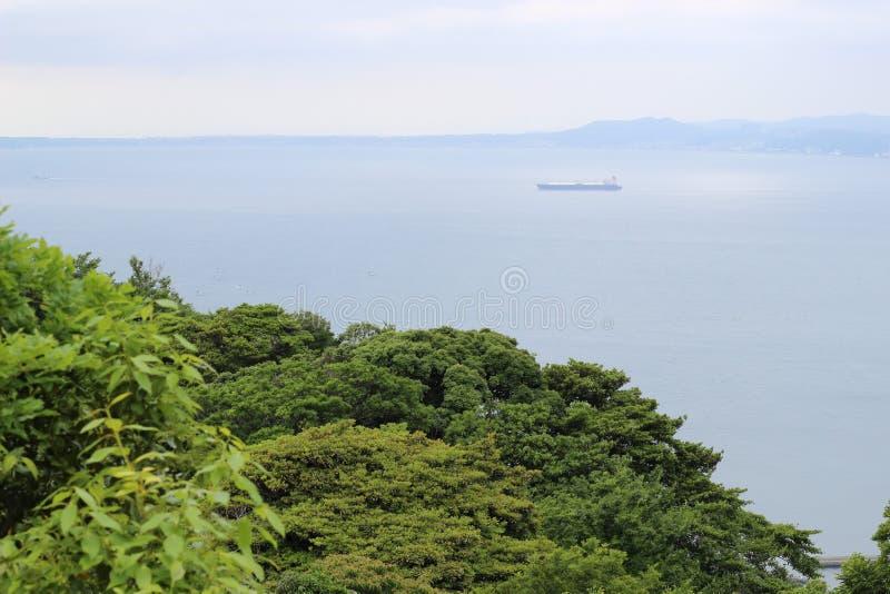 在海的一艘孤立船有在前景的有些树的 图库摄影