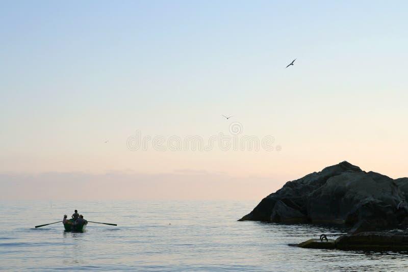 在海的人划船日落的 在天空的鸥 图库摄影