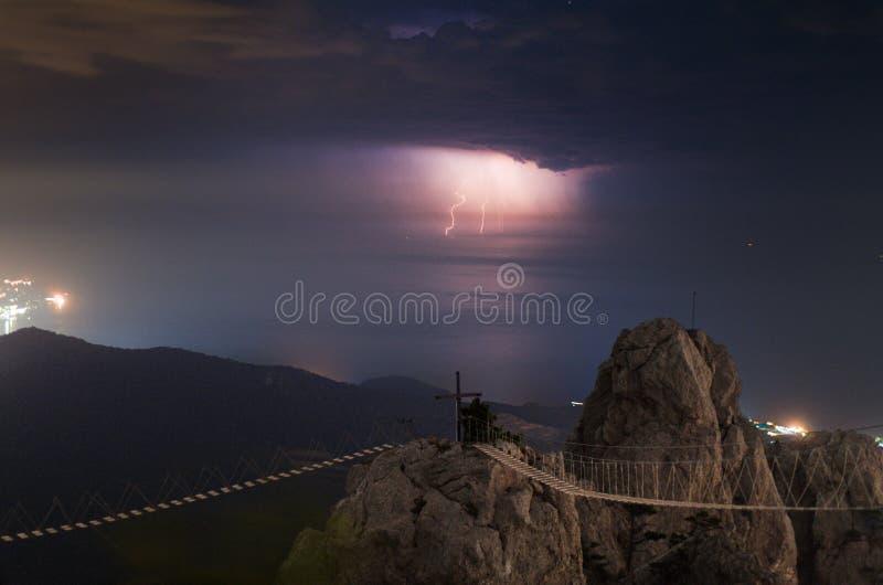 在海的夜雷暴 对黑海水的闪电  落矶山脉峭壁 向Ai的垂悬的道路 免版税库存图片