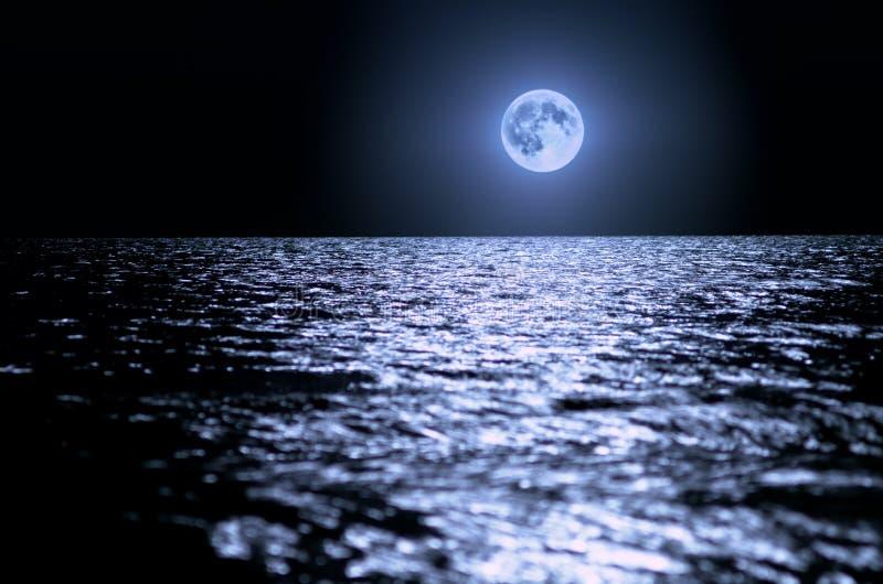 在海的大月亮在晚上 在波浪的月光,天际 长期风险 免版税库存照片