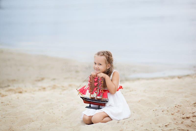 在海的女孩有船的 女孩的面孔的特写镜头画象 女孩有猩红色风帆的等待小船 海滩的女孩在a 库存图片