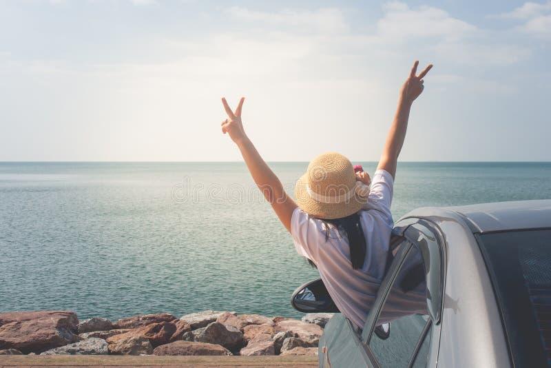 在海的家用汽车旅行,快乐画象的妇女举她的手和感觉幸福 库存图片