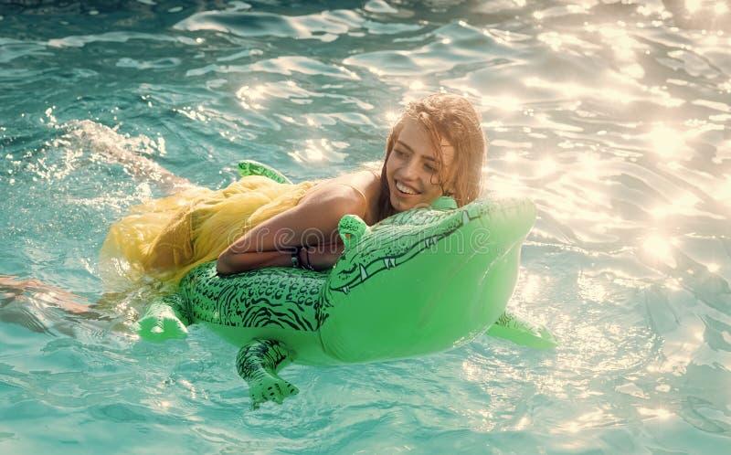 在海的性感的妇女有可膨胀的床垫的 时尚鳄鱼皮革和女孩在水中 放松在豪华游泳池 免版税库存图片