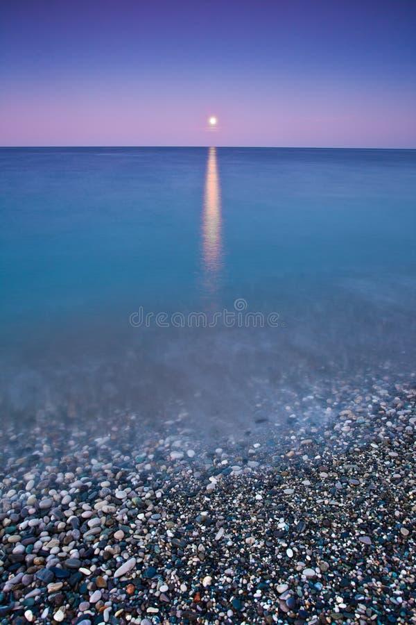 在海的日落月亮,海浪被月光照亮道路 库存照片