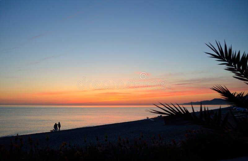 在海的日落有海滩和人民的剪影的 免版税库存照片