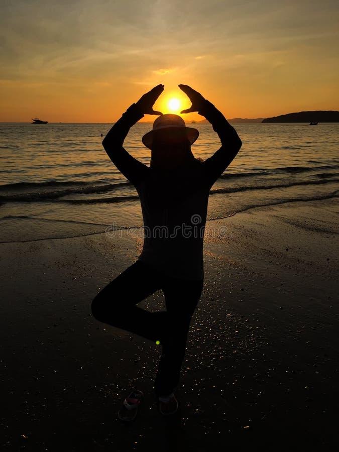在海的日落陪同的妇女 库存图片