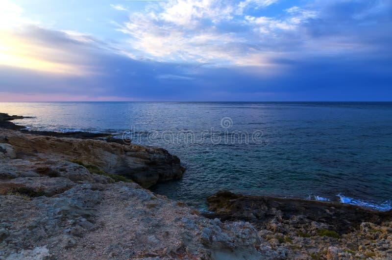 在海的明亮的五颜六色的日落有美丽的云彩的和有在火山岩的水坑的在前景 免版税图库摄影