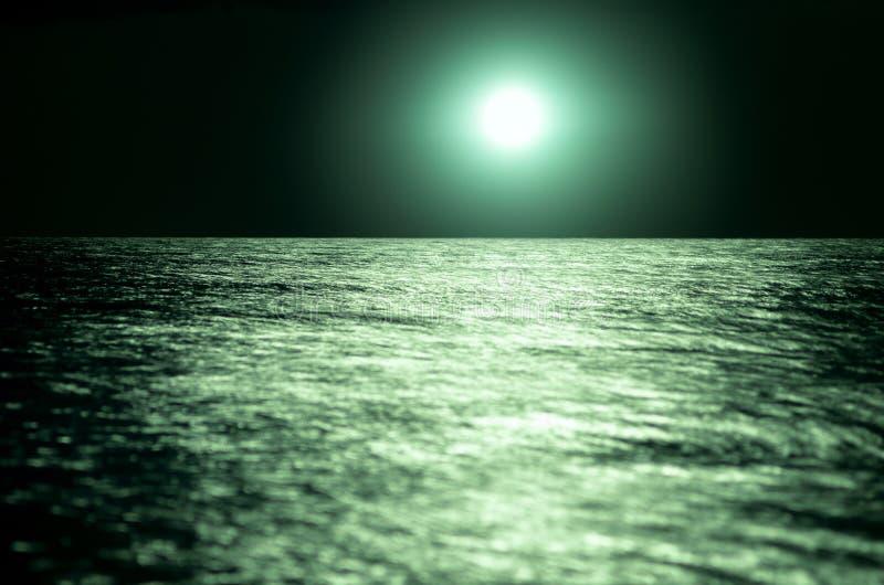 在海的明亮的月亮绿色在晚上 在波浪的月光,天际 长期风险 库存照片