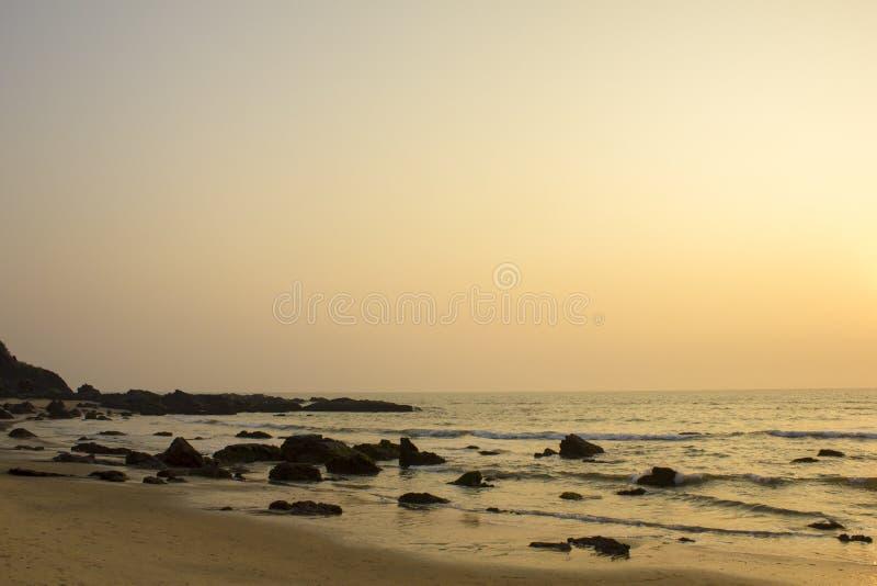 在海的桃红色灰色清楚的日落天空反对与岩石的一个沙滩在海洋 库存图片