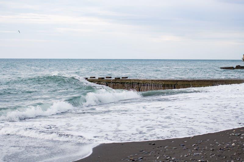 在海的波浪在码头阴云密布附近 免版税图库摄影
