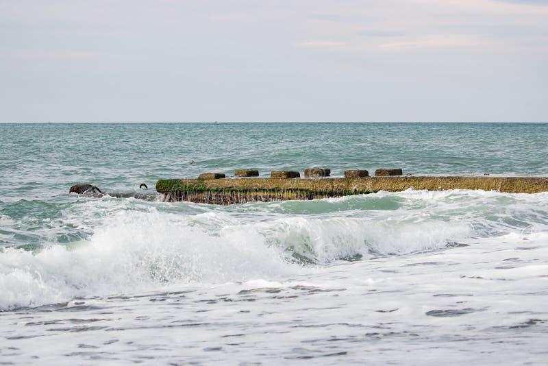 在海的波浪在码头阴云密布附近 免版税库存照片