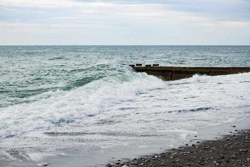 在海的波浪在码头阴云密布附近 图库摄影