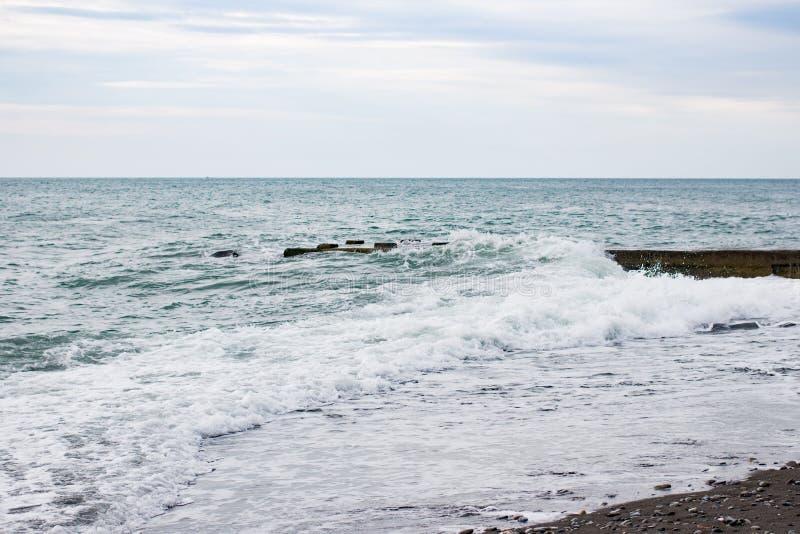 在海的波浪在码头阴云密布附近 库存图片